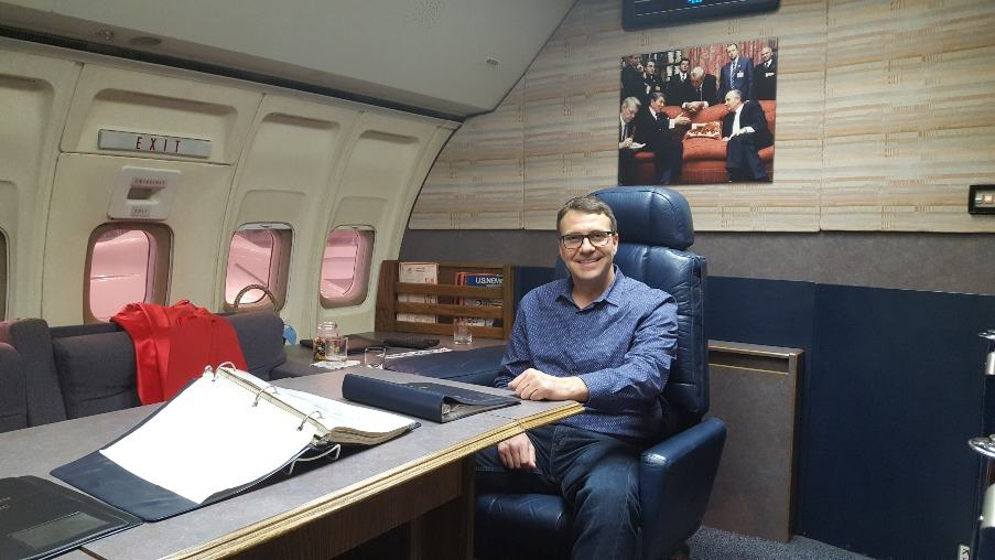 Tom Smith sits at Conference table aboard Air Force One