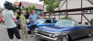 classic and vintage cars on the street in downtown solvang for wheels and windmills car show with spectators present
