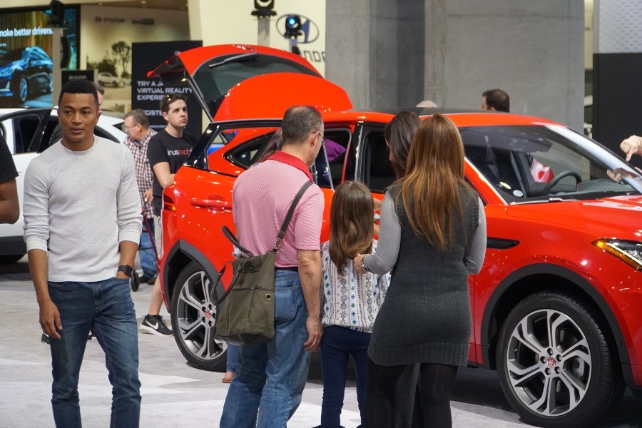 San Diego International Auto Show dude walking by, family checking out suv on showroom floor