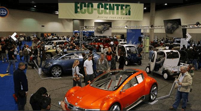 orange two-door car inside San Diego International Auto Show