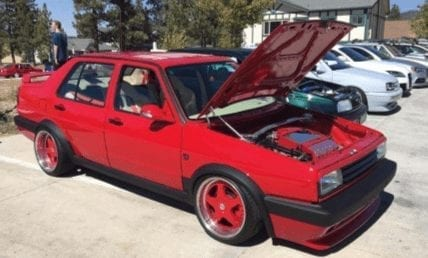 Red Custom VW Jetta parked with hood propped open