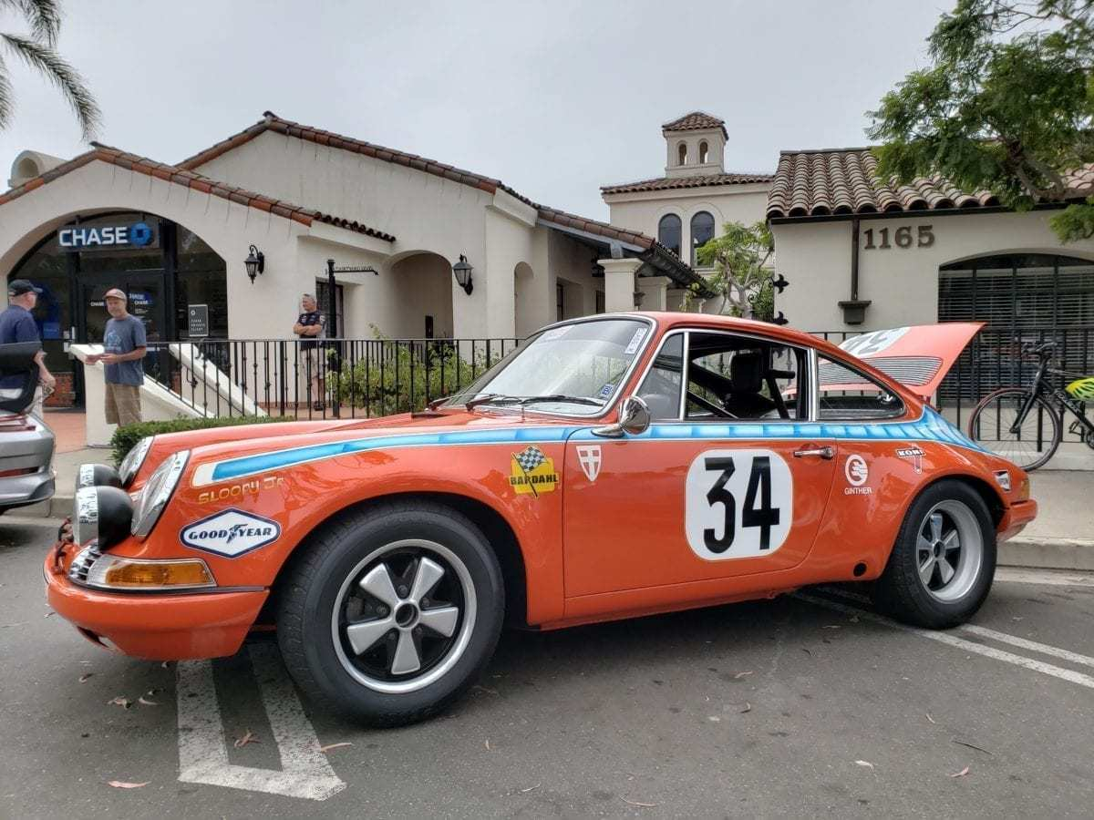 Orange with blue stripe and number 34 on the door, 1971 Porsche 911 parked at the Montecito Motor Classic
