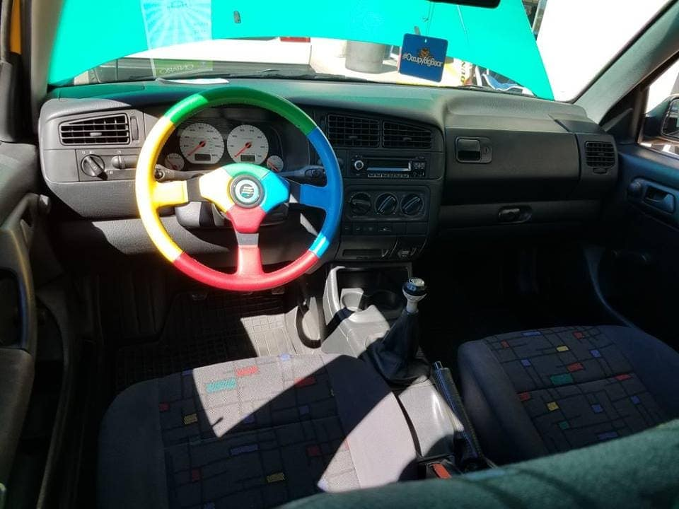 Interior front seats and dashboard of a parked Volkswagen multi-colored Golf. The seats are gray with yellow, red, green and blue squares separated by black lines - Andy Warhool-ish. The steering wheel is green, yellow, blue and red.