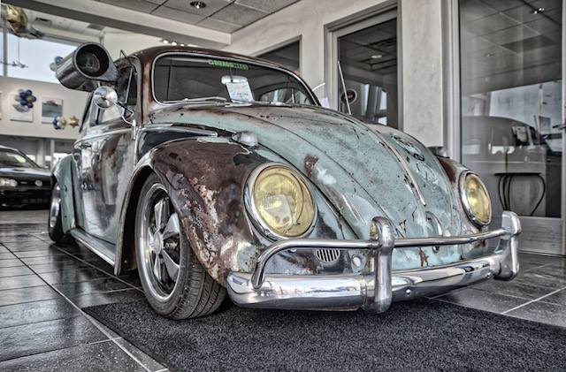 Retro, high-contrast, altered image of a classic Volkswagen Beetle painted to look old and weathered but truly in pristine condition parked in Ontario VW car dealership