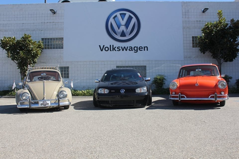 Three forward facing Volkswagen vehicles parked in front of Ontario Volkswagen car dealership. The middle VW is newer and black the VW on the left is a classic Beetle and beige in color and the one on the right is also a classic VW and orange in color