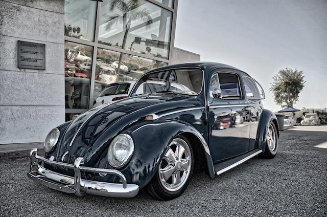 Retro, high-contrast image of a parked classic Volkswagen Beetle slightly lowered but still original looking and completely immaculate. Windows open and very shiny - freshly polished.