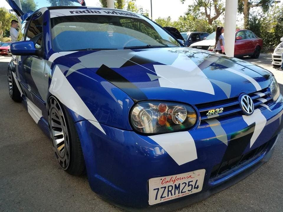 Parked Volkswagen race car with cool paint job. Royal blue, with white, black and gray sharp-edged shapes throughout.