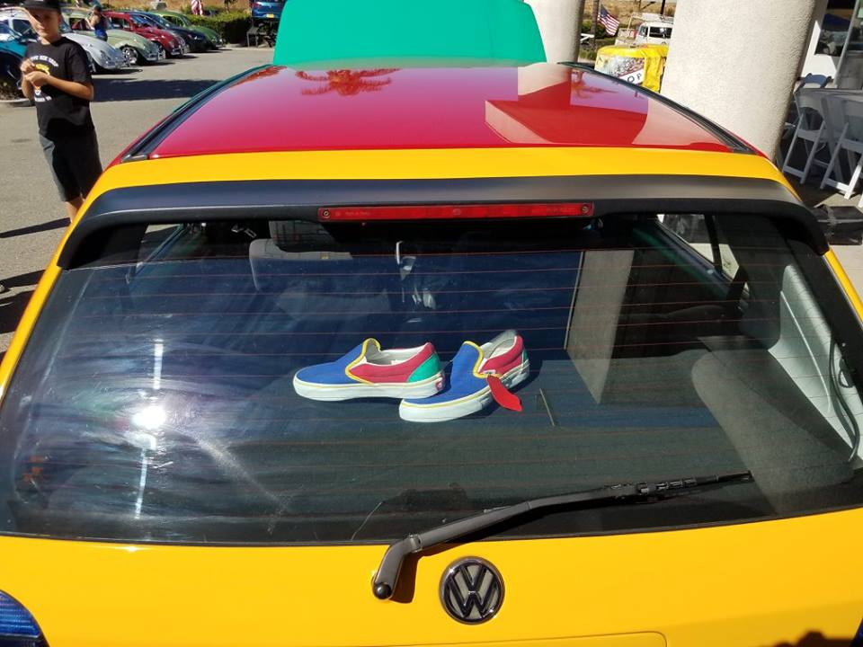 Parked multi-colored Volkswagen Golf - rear view. Slip on Vans shoes are pictured sitting on the rear dash and the shoes are the same multi-colors as the car - blue, yellow, red and green.