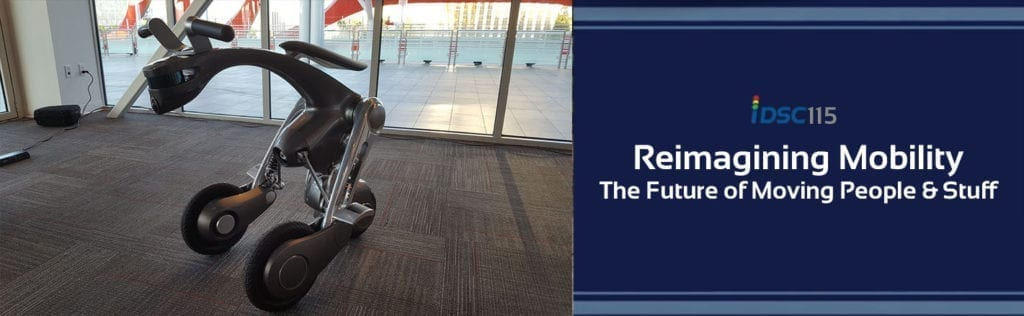 Picture of a robotic kangaroo sitting on the floor of an office as part of an iDriveSoCal 115 banner stating Reimaging Mobility The Future of Moving People & Stuff