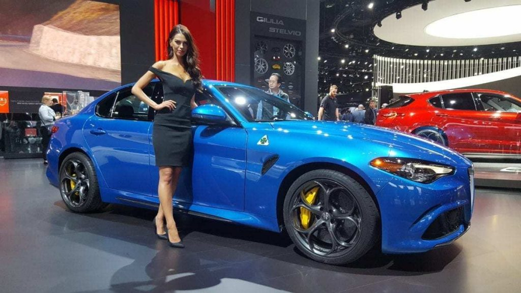 Blue Alfa Romeo Giulia Quadrifoglio with beautiful woman leaning against it at the Los Angeles Auto Show