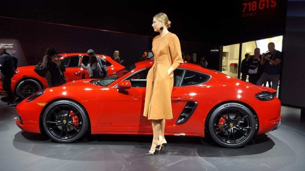 Red Porsche 718 Cayman GTS with beautiful female model at the Los Angeles Auto Show