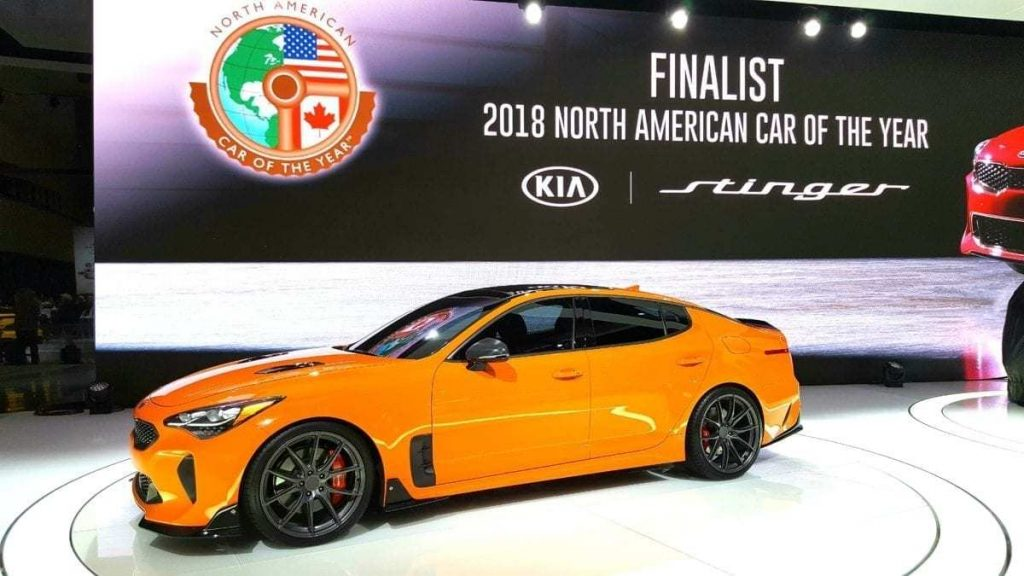 Orange Kia Stinger GT2 parked in front of Finalist 2018 North Amerian Car of the Year at the LA Auto Show