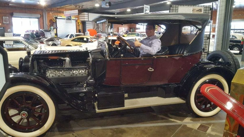 Tom Smith sits with thumbs-up in an antique car parked inside The Automobile Driving Museum