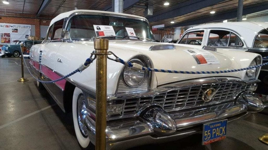1955 Classic convertible parked in The Automobile Driving Museum with a white top and three-tone paint - white, pink and black