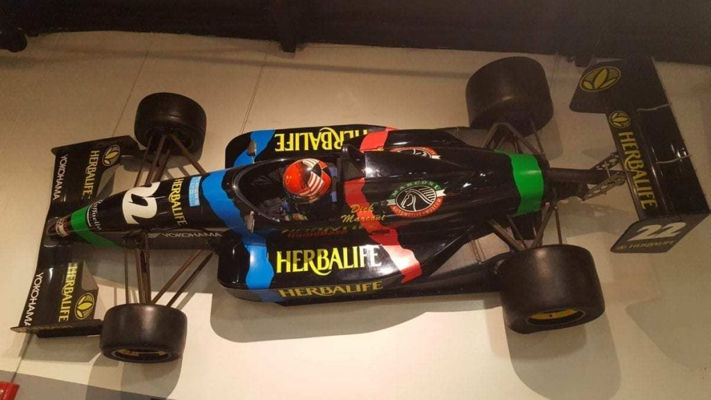Black open-wheeled Herbalife racecar mounted on the wall inside The Marconi Automotive Museum