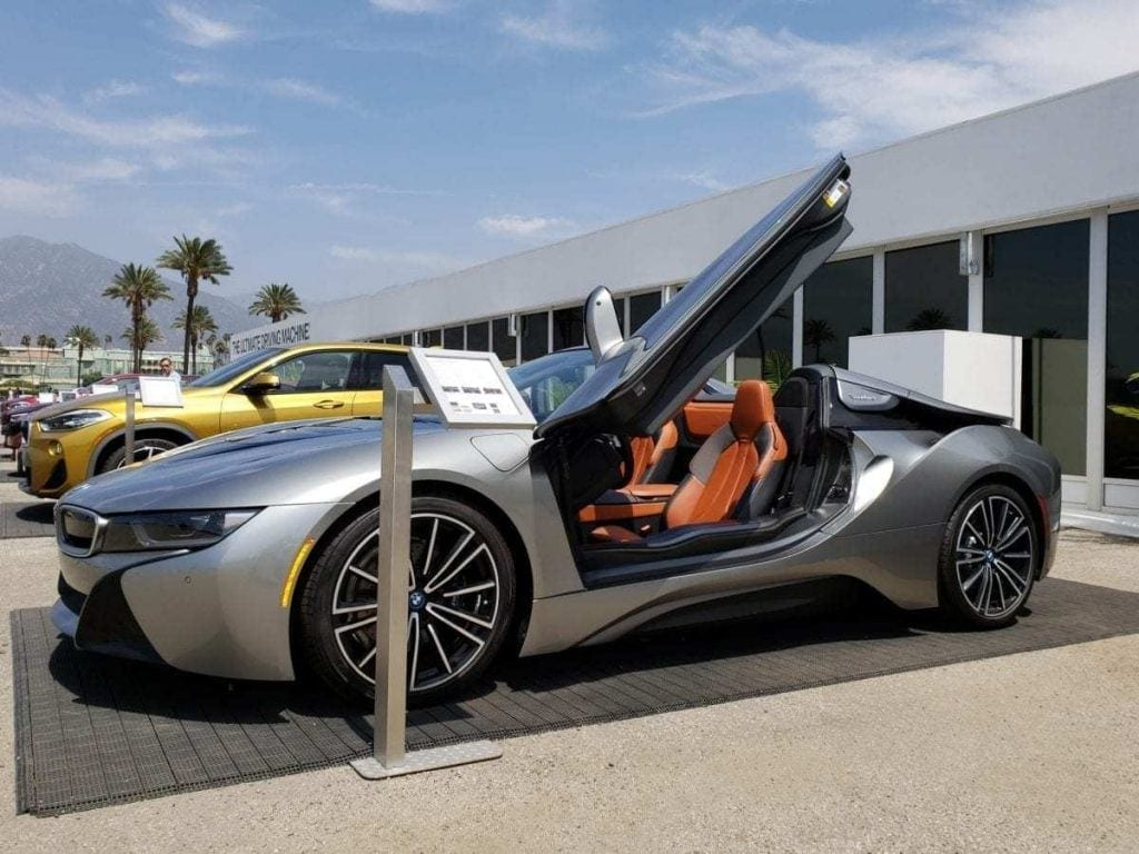 Silver BMW i8 Roadster parked with driver-side butterfly door open