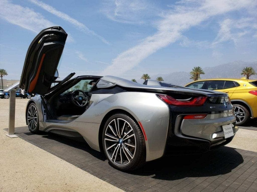 Silver BMW i8 Roadster parked with driver's butterfly door open