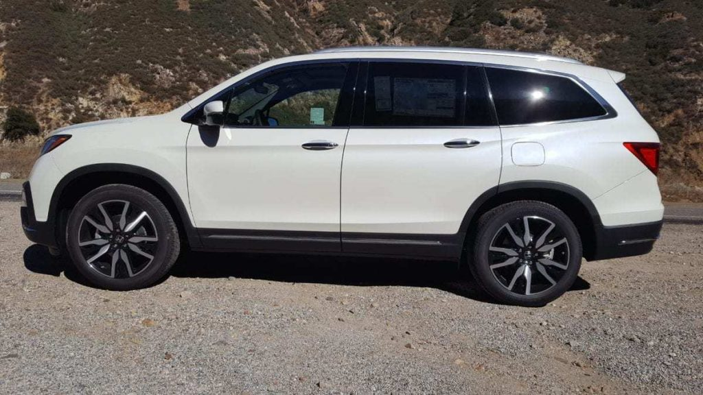 Driver's-side profile of a parked white 2019 Honda Pilot