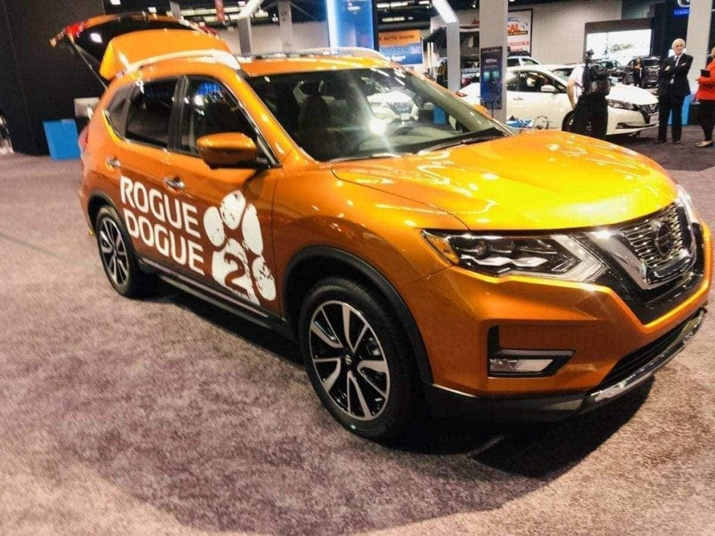 Orange 2019 Nissan Rogue Dogue 2 pictured w/ rear hatch door open on the floor of the Orange County International Auto Show