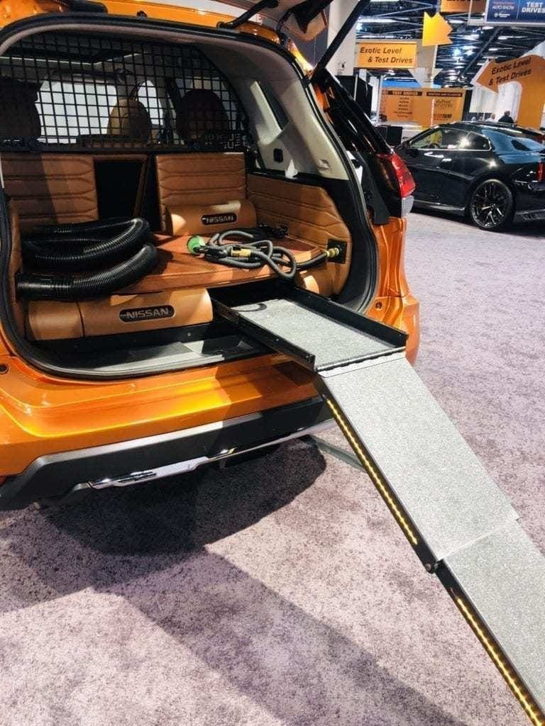 Opened up rear of the 2019 Nissan Rogue Dogue Concept vehicle at the Orange County International Auto Show pictured with a dog ramp from the groud to the back of the vehicle. Dog cleaning equipment also shown in the rear compartment of the vehicle.