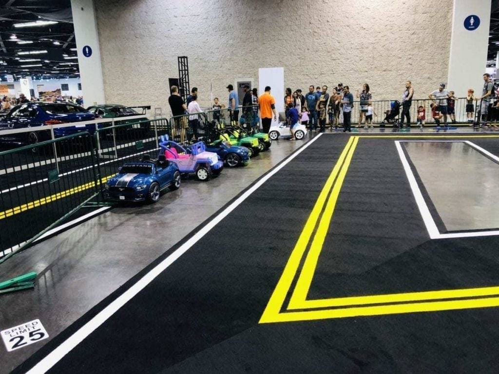 Electric Toy Cars and carpeted roads pictured with parents and kids in line for the Kiddie Ride & Drive @ the Orange County International Auto Show