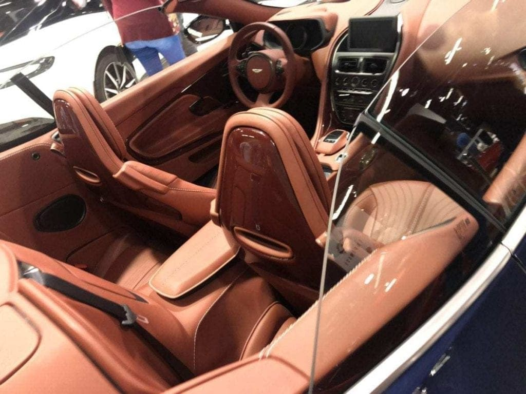 Rust colored leather trimmed interior of a 2019 Aston Martin with convertible top down pictured at the Orange County International Auto Show