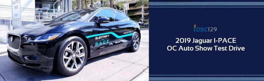 Parked black 2019 Jaguar I-PACE Electric compact Crossover SUV with a blue strip down the side at the Orange County International Auto Show pictured in the iDriveSoCal Podcast 129 banner