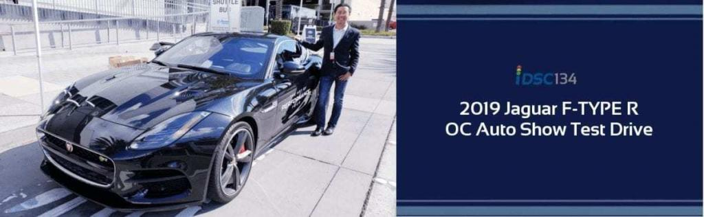 Black 2019 Jaguar F-TYPE R parked outside the Orange County International Auto Show with iDriveSoCal's Professor, Clinton Quan, standing next to it as part of the iDSC134 Test Drive Podcast banner