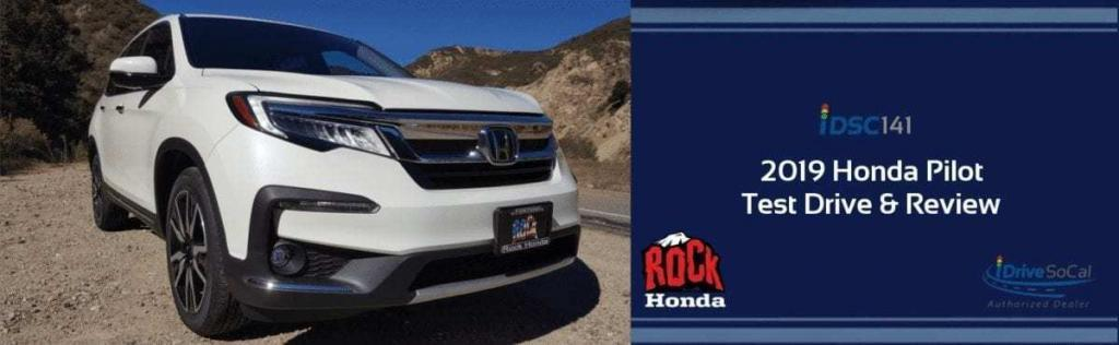 Front-passenger-side view of a white 2019 Honda Pilot parked as party of the iDriveSoCal Podcast banner 141 Test Drive and Review