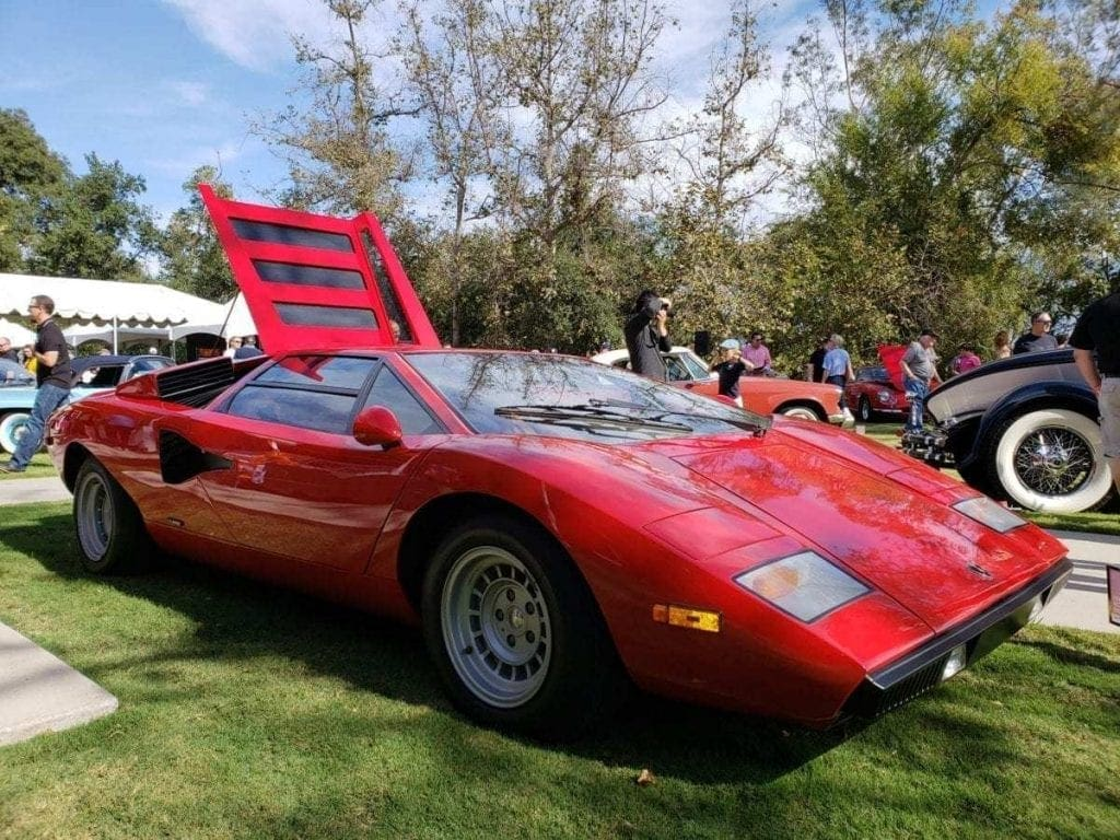 Classic red Lamborghini Countach parked on the grass at the ArtCenter Car Classic