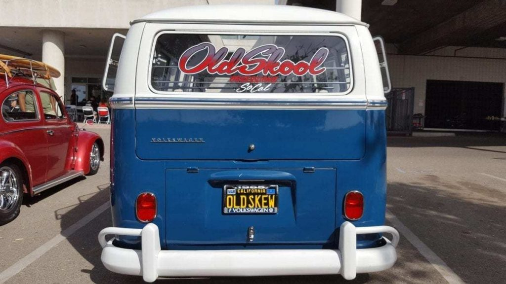 Rear-facing white on blue, classic, custom, Volkswagen Bus with Old Skool Obsessionz lettering in window