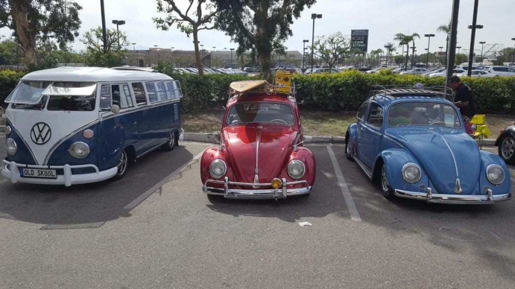 Line-up of three beautiful classic Volkswagen's - a blue and white Bus, a red Bug with surf board and cooler on it's roof rack and a light blue Bug
