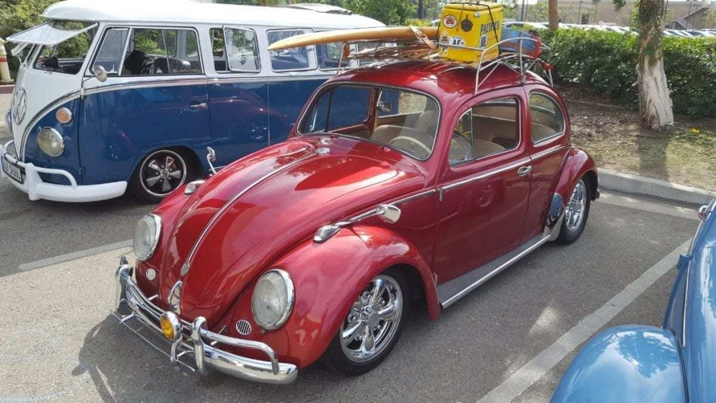 Front-driver-side view of a classic, cherry red, VW Bug and a classic white & blue VW Window Bus in the background parked @ Ontario Volkswagen during Oktoberfest Car Show