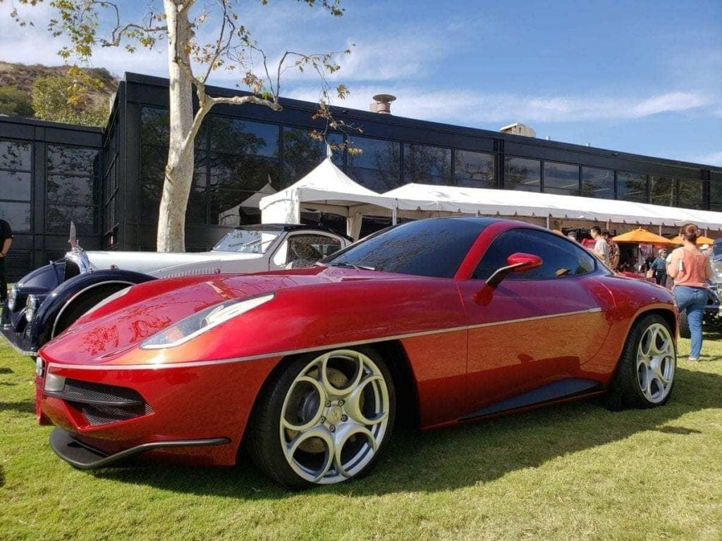Futuristic looking red sport coupe concept vehicle with tinted windows parked in the grass of the ArtCenter Car Classic