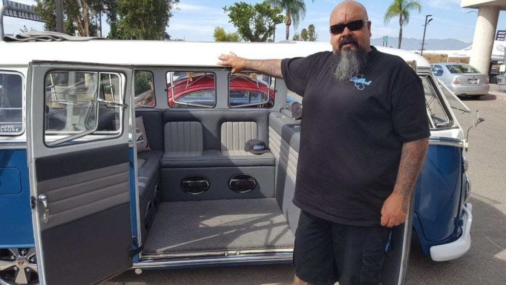 Old Skool Car Club Founder stands beside his white and blue custom classic VW Window