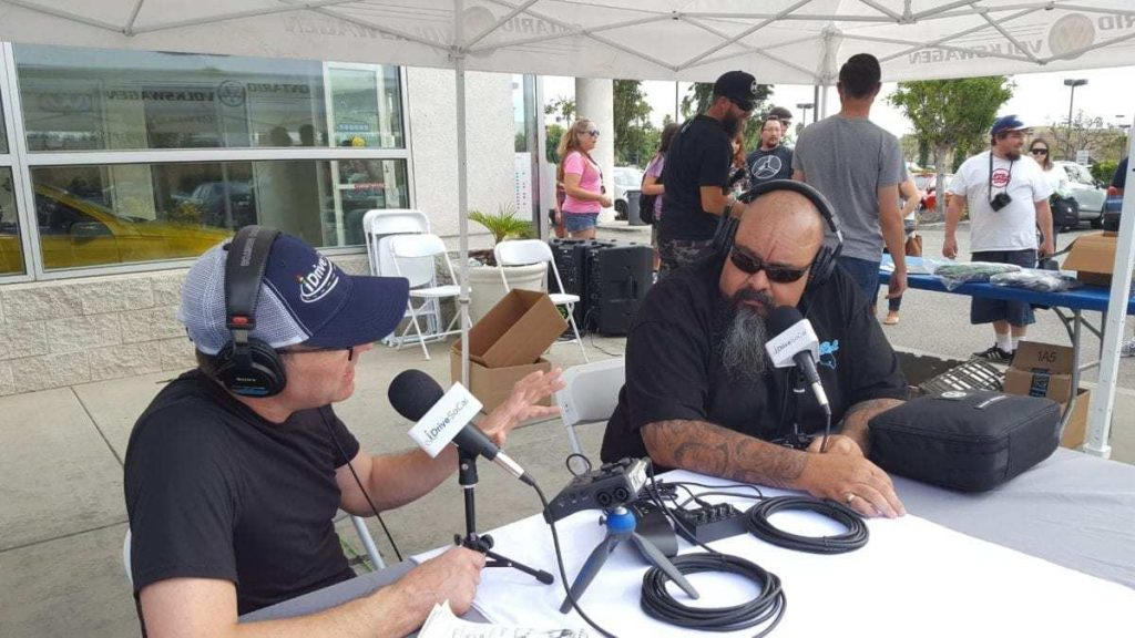 Danny Aceves of Old Skool Car Club is interviewed by Tom Smith of iDriveSoCal during Oktoberfest Auto Show at Ontario Volkswagen