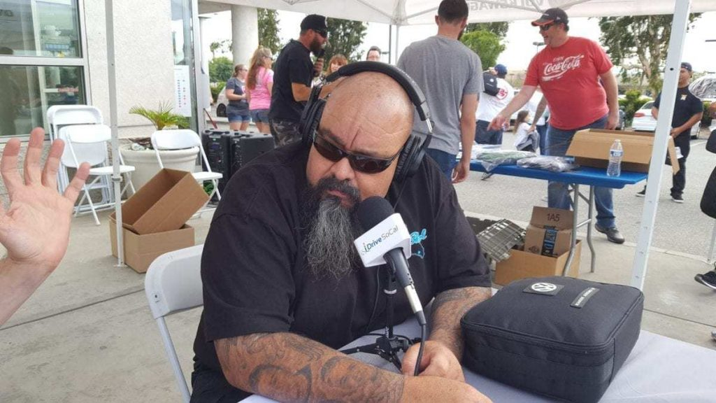 Danny Aceves at iDriveSoCal microphone being interviewed during Oktoberfest Car Show at Ontario VW