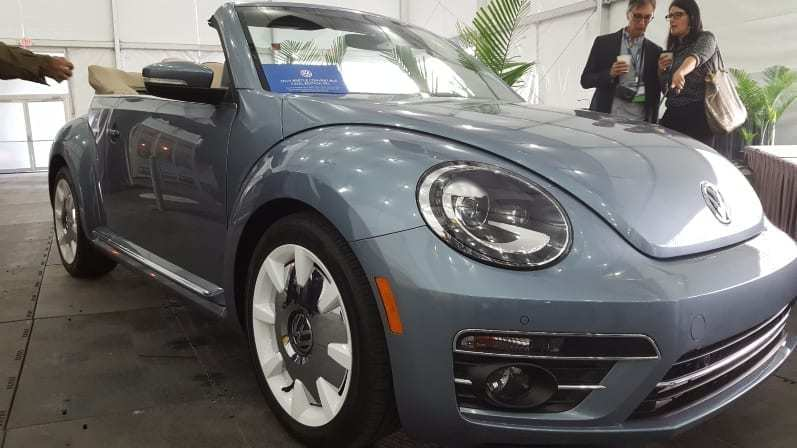 Gray 2019 VW Beetle Convertible w/ top down and show attendees pointing and taking pictures