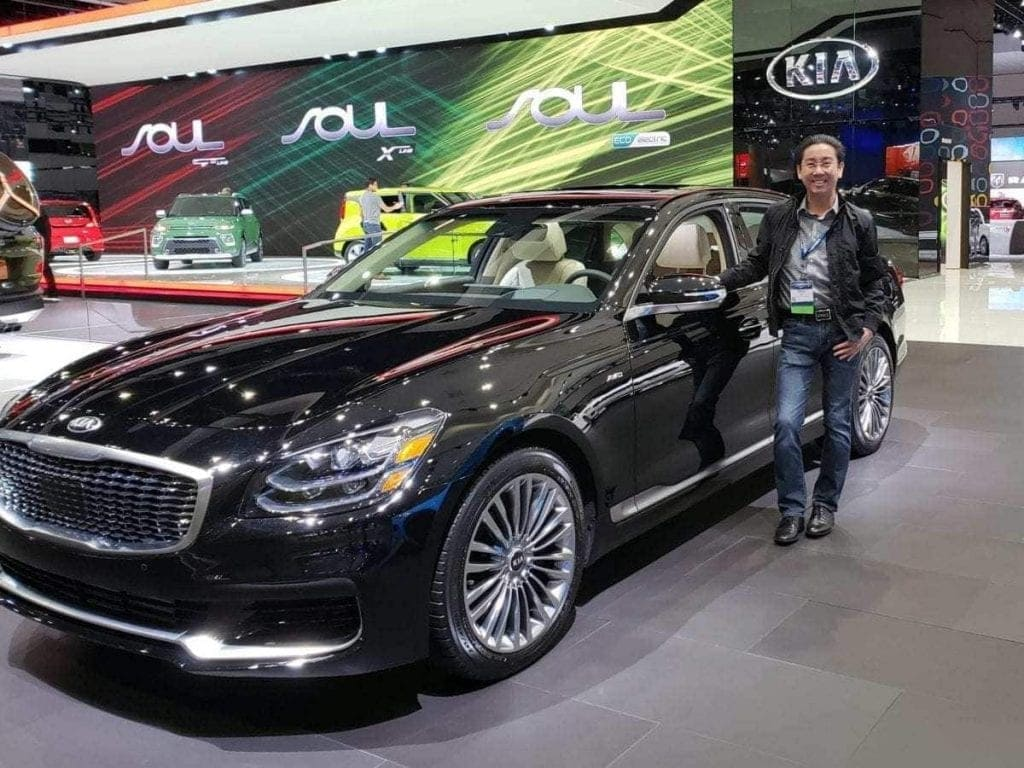 iDriveSoCal's Professor Quan stands next to a black KIA K900