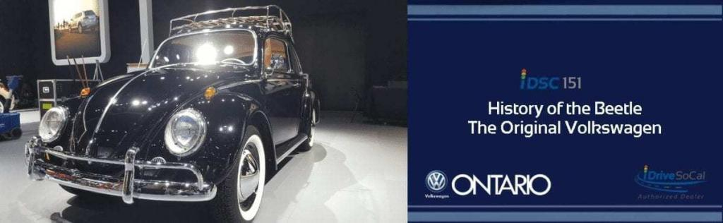 Black classic Volkswagen Beetle parked on stage being prepared for the LA Auto Show as part of the iDriveSoCal 151 Podcast banner sponsored by Ontario VW