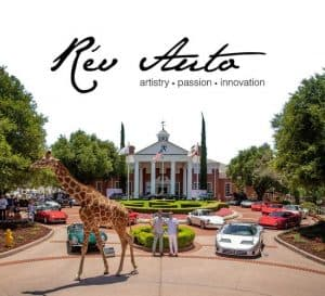 Giraffe walks by excotic and classic cars in front of estate.