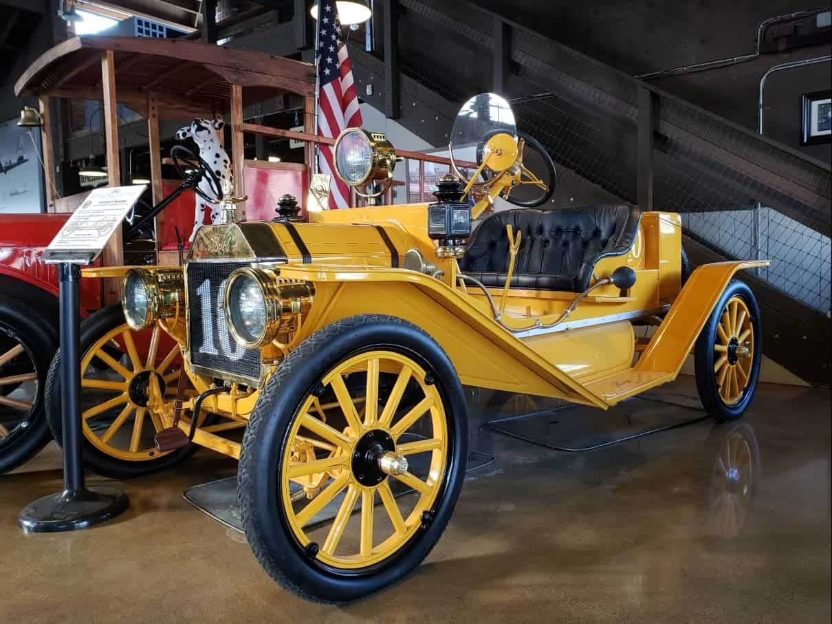 Yellow antique open air hand-crank car - Motte Historical Car Museum