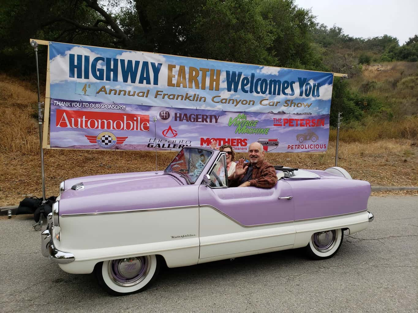 Nash Metropolitan with man and woman wave to camera