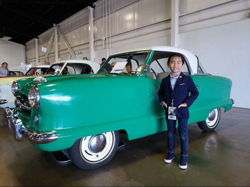 Little boy stands in front of a lime green Nash Metropolitan