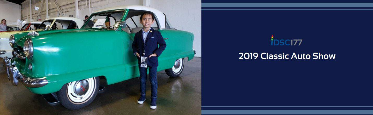 Small boy stands next to small classic car pictured as part of the 2019 Classic Auto Shot podcast banner from iDriveSoCal