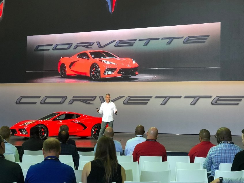Executive speaks on stage w. 2020 Chevy Corvette Stingray