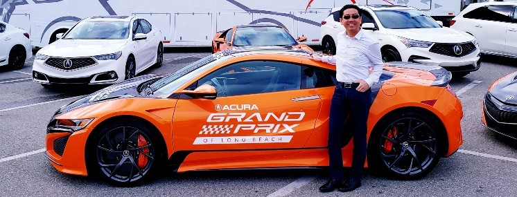 Professor Quan strikes a pose at Long Beach Grand Prix banner