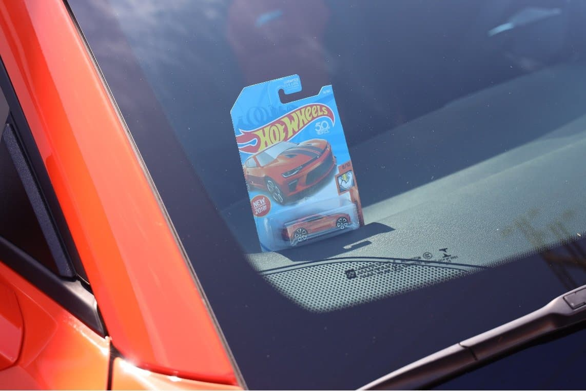 Hot Wheels Toy Car on the Dashboard of Life-Sized Replica