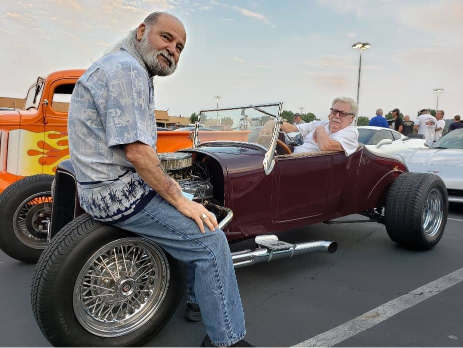 Man sits on front wheel of hot rod at Cars And Coffee Valencia